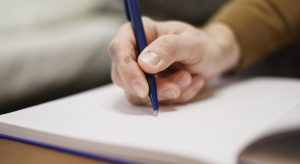 Photo of a hand writing in a notebook